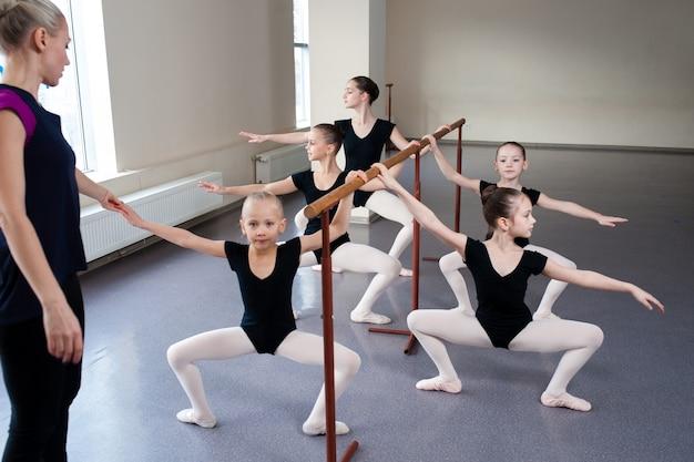 As crianças aprendem posições de balé na coreografia.