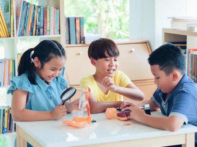 As crianças asiáticas agrupam alegre na classe de biologia. conceito de escola em casa.