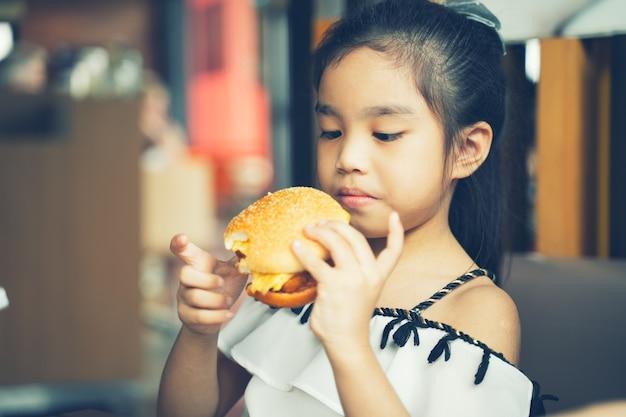 As crianças asiáticas comem queijo de frango hamburger food court