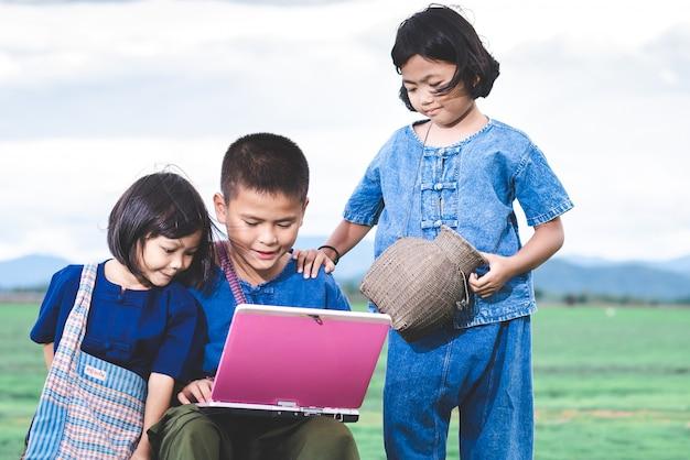 As crianças asiáticas em trajes locais estão usando o laptop para educação e comunicação na zona rural da tailândia.