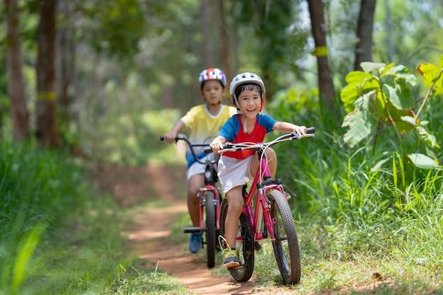 As crianças asiáticas estão felizes com o mountain bike.