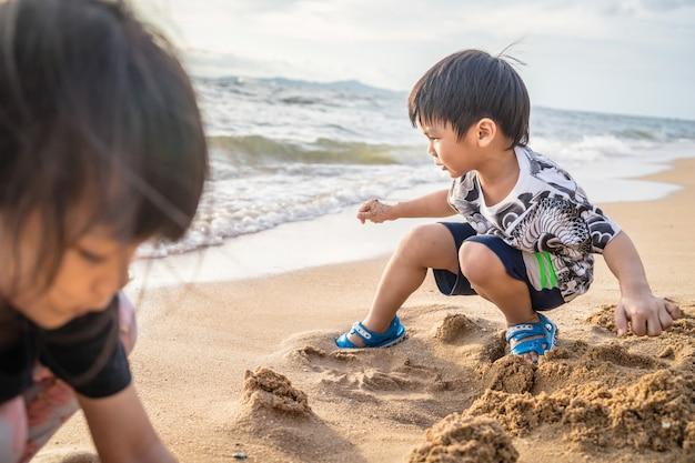 As crianças asiáticas estão jogando areia na praia