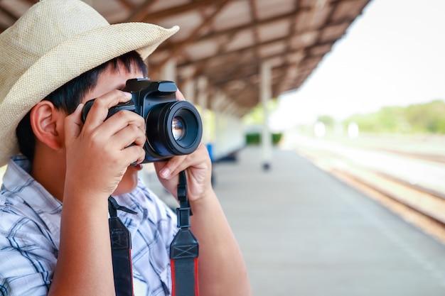 As crianças asiáticas estão tirando fotos com uma dslr. viajar de trem.