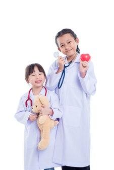 As crianças asiáticas novas fingem ser doutor que está sobre o fundo branco