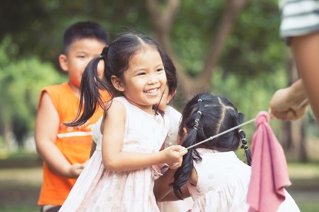 As crianças asiáticas se divertem para jogar o conflito com a corda juntos no parque em tom de cor vintage