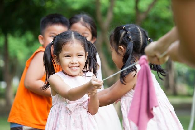 As crianças asiáticas se divertem para jogar o conflito com a corda juntos no parque
