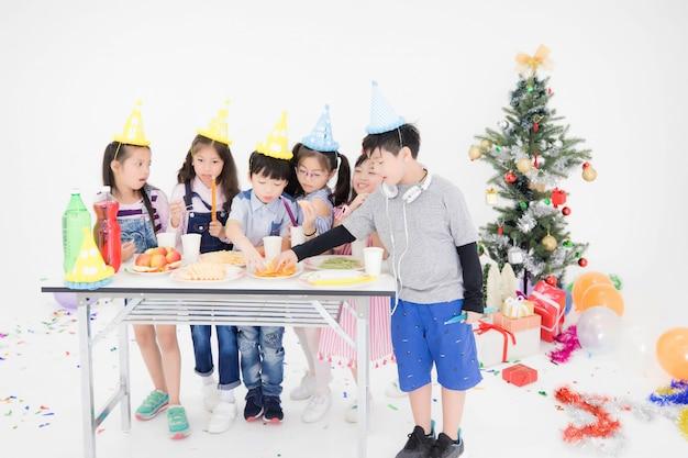 As crianças asiáticas tailandesas usam um vestido casual, comem lanches e se divertem em uma festa de natal.