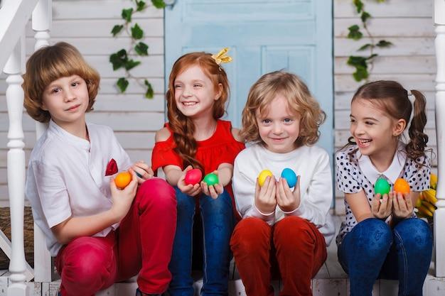 As crianças bonitas sentam-se perto da cesta com tulipas e guardam-se ovos da páscoa em suas mãos.