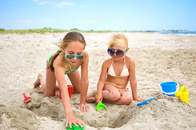 As crianças brincam com areia na praia.
