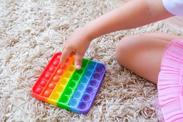 As crianças brincam com o brinquedo sensorial pop it. alívio do estresse e da ansiedade. um jogo de silicone para crianças e adultos estressados. brinquedos de bolha macios e macios.