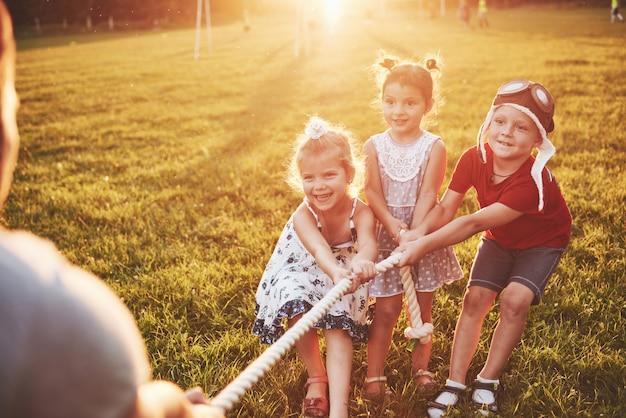 As crianças brincam com o pai no parque. eles puxam a corda e se divertem em um dia ensolarado