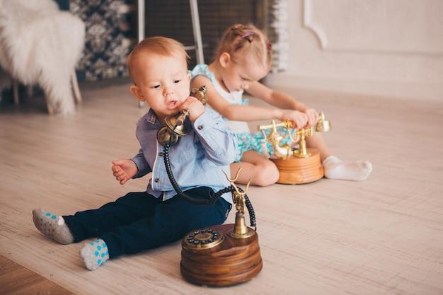 As crianças brincam com o telefone no chão. conceito de negócio para iniciantes. negociação de negócios