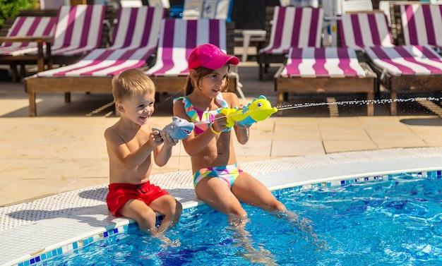 As crianças brincam com pistolas de água na piscina. foco seletivo. água.
