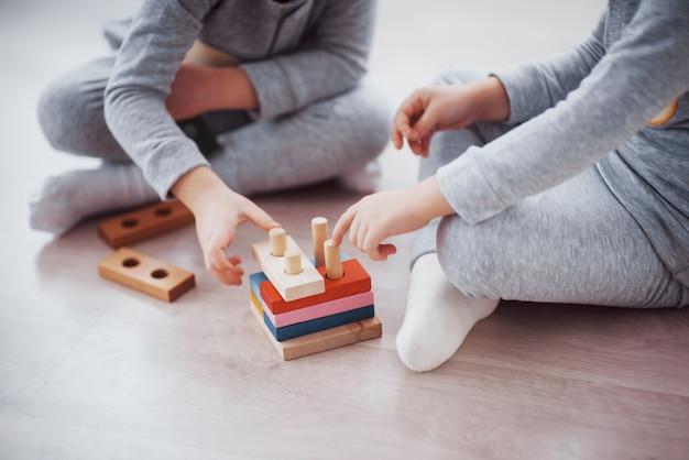 As crianças brincam com um designer de brinquedos no chão do quarto das crianças.