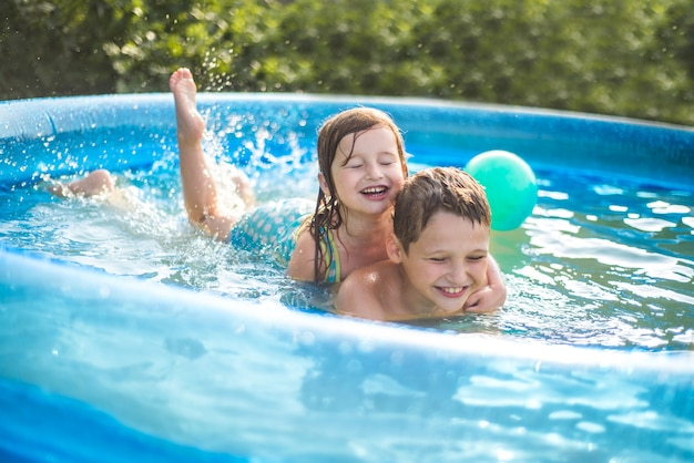 As crianças brincam com uma bola na piscina no verão quente. menina e menino. menina bonitinha na piscina ao ar livre