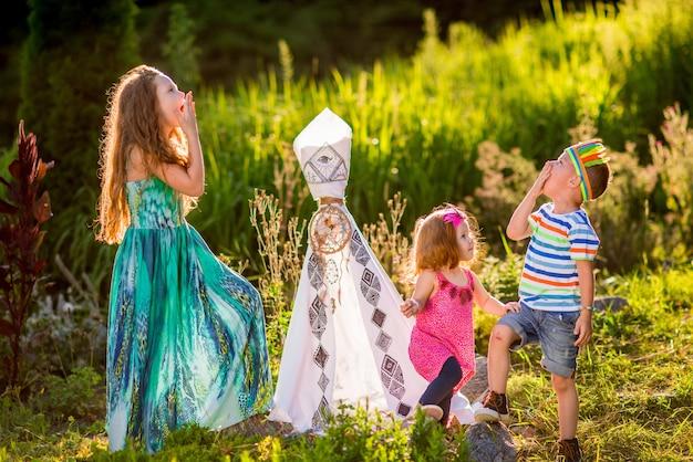 As crianças brincam como aborígene americano na grama verde no campo
