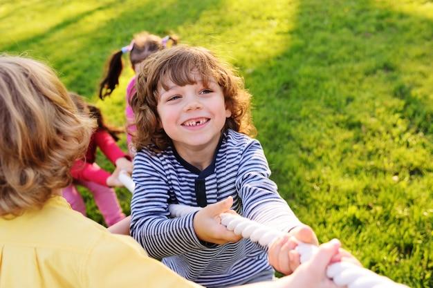 As crianças brincam de cabo de guerra no parque.
