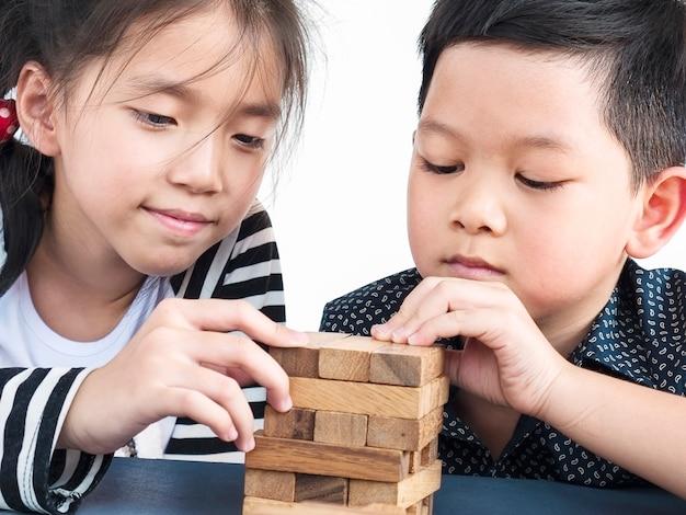 As crianças brincam de jenga, um jogo de torre de blocos de madeira