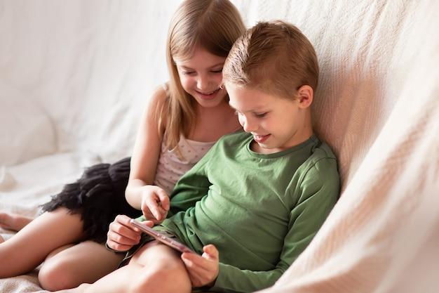 As crianças brincam de telefone, assistem a vídeos em aparelhos deitados no sofá
