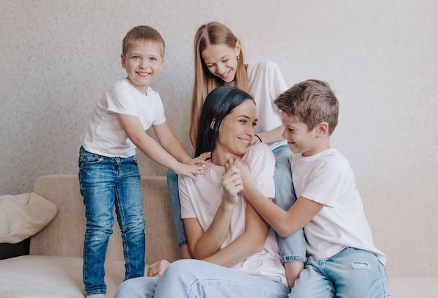 As crianças brincam e brincam com a mãe sentada em casa no sofá. mãe feliz, relacionamentos familiares perfeitos e felizes.