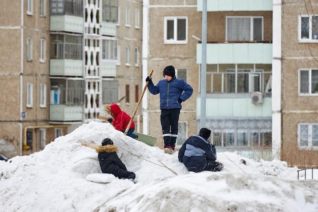 As crianças brincam em um monte de neve suja no inverno. ecologia pobre