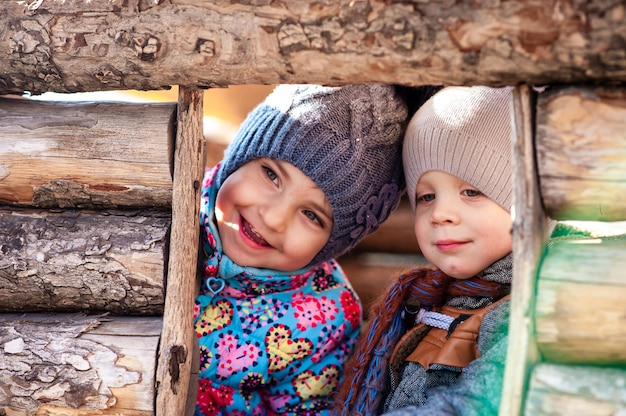 As crianças brincam em uma casa de madeira