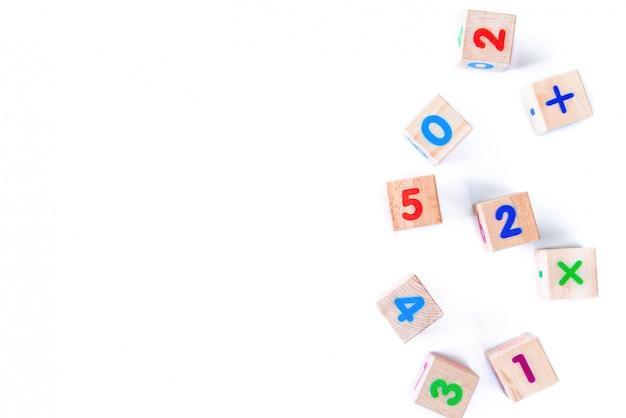 As crianças brincam filhotes de madeira com números no fundo branco. desenvolvimento de blocos de madeira. brinquedos naturais e ecológicos para crianças. vista do topo. postura plana. copie o espaço.