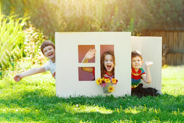 As crianças brincam na casa feita de caixa de papelão