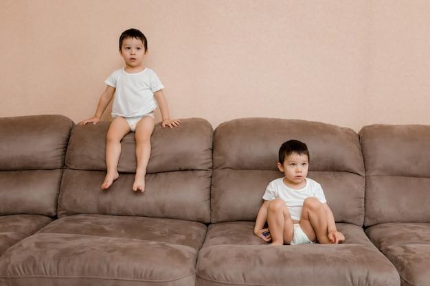 As crianças brincam na sala em casa. gêmeos de dois anos pulam no sofá