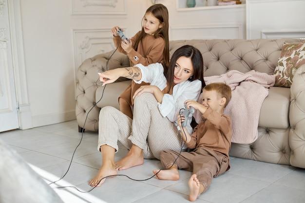 As crianças brincam no console com a mãe.