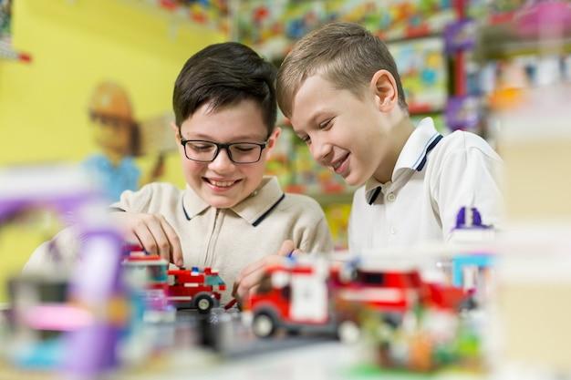 As crianças brincam no designer à mesa. dois meninos brincam juntos com blocos de plástico coloridos no centro de jogos, escola.