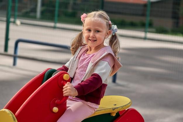 As crianças brincam no parque infantil. uma garota feliz e sorridente se diverte balançando e escalando ao ar livre