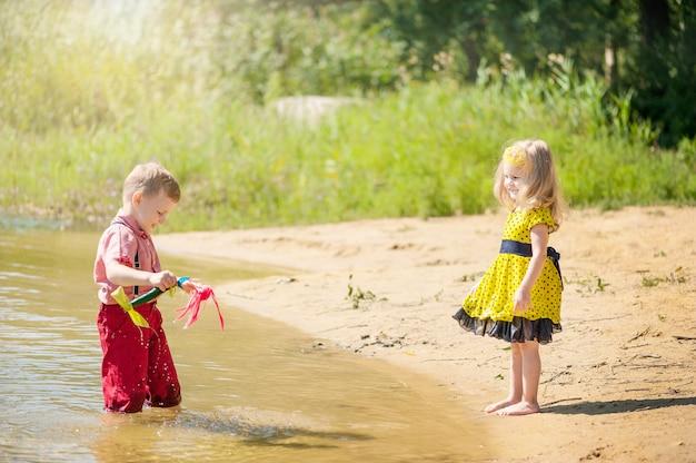 As crianças brincam no rio com barcos