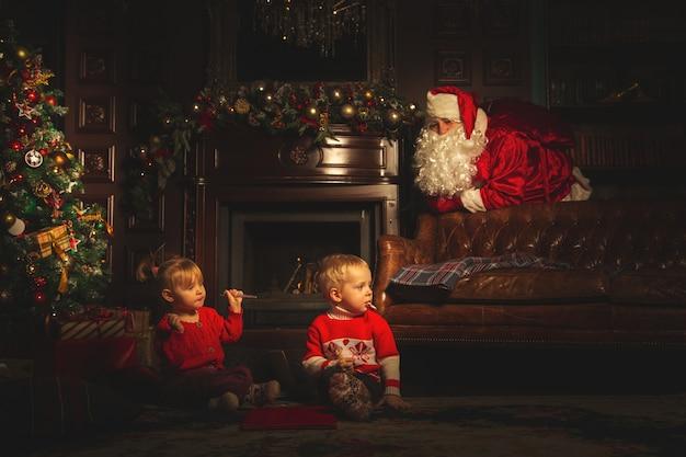 As crianças brincam perto da árvore de natal. o verdadeiro papai noel está observando-os.