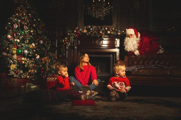 As crianças brincam perto da árvore de natal. o verdadeiro papai noel os observa.