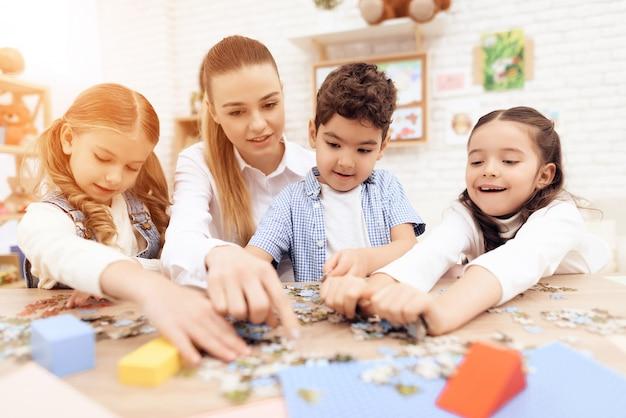 As crianças colocam quebra-cabeças junto com adultos.