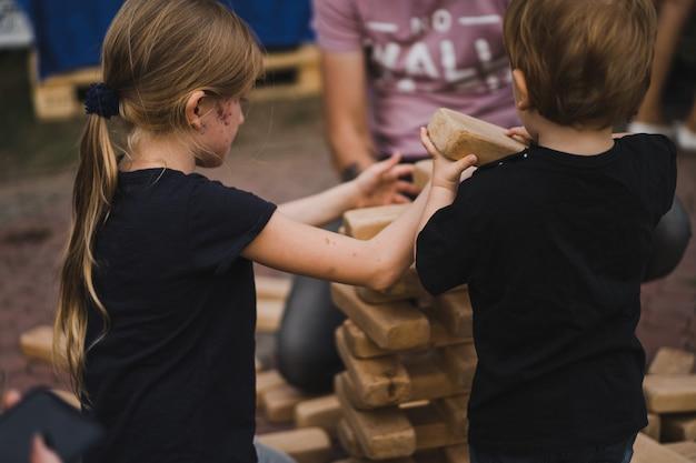 As crianças colocam uma pirâmide de cubos