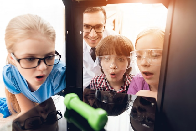 As crianças com o professor olham como a impressora 3d impressa o peso.