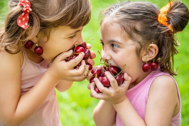 As crianças comem cerejas no verão