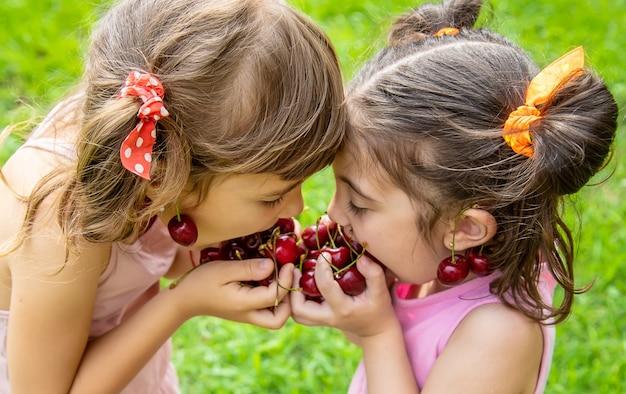 As crianças comem cerejas no verão.