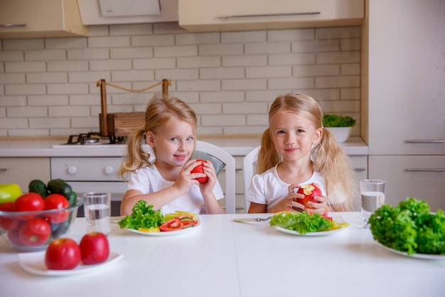 As crianças comem comida saudável na cozinha