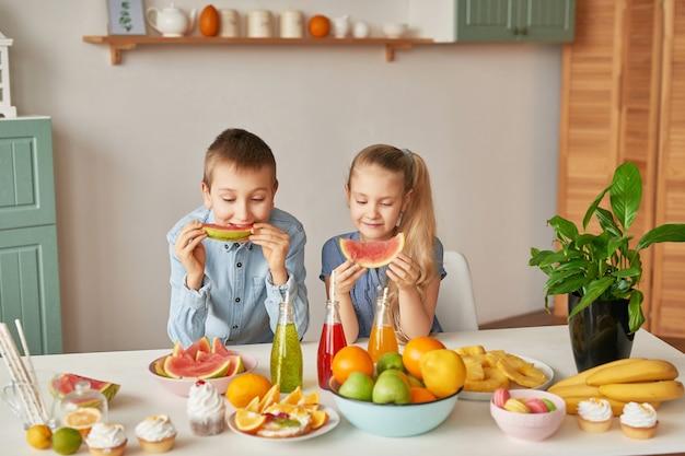 As crianças comem fatias de melancia na cozinha