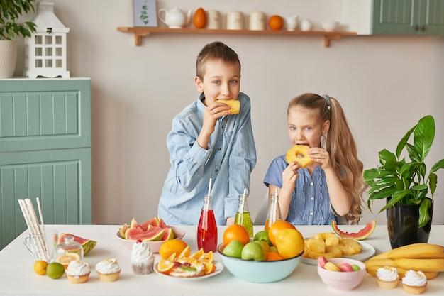 As crianças comem frutas em uma mesa cheia de comida