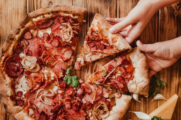 As crianças comem pizza com salame e mussarela