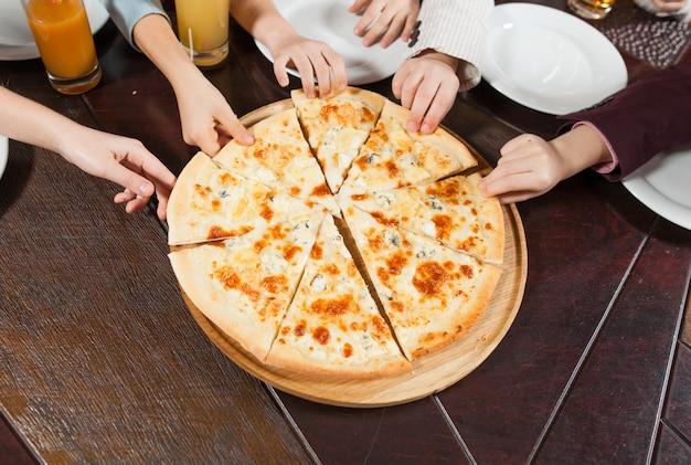 As crianças comem pizza em um restaurante.