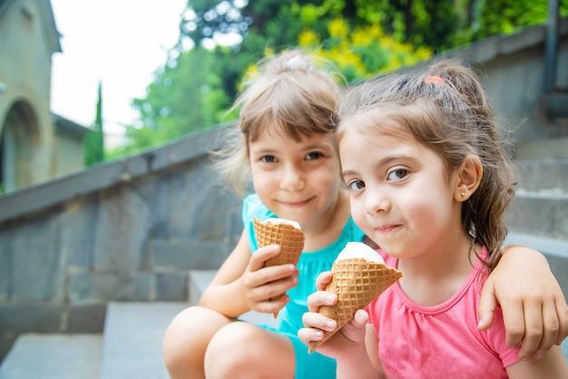 As crianças comem sorvete no parque.