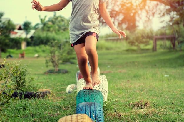 As crianças correm jogando pneus no recreio