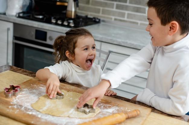 As crianças cozinham biscoitos de natal e riem umas das outras