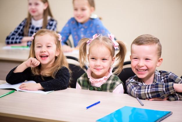 As crianças da escola primária trabalham juntas na classe.