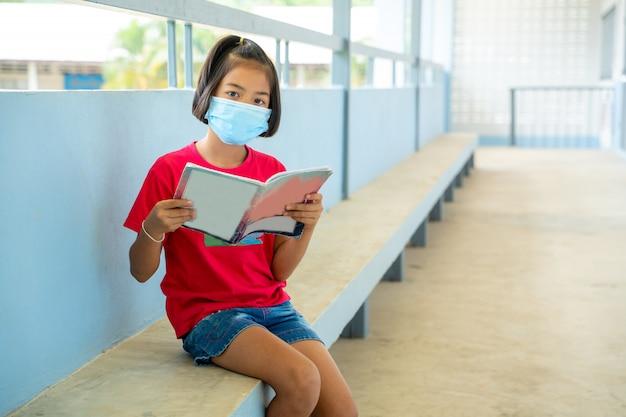 As crianças da escola usam máscaras protetoras para segurança, sentado na escola primária, educação, aprendizagem e conceito de pessoas, distanciamento social.